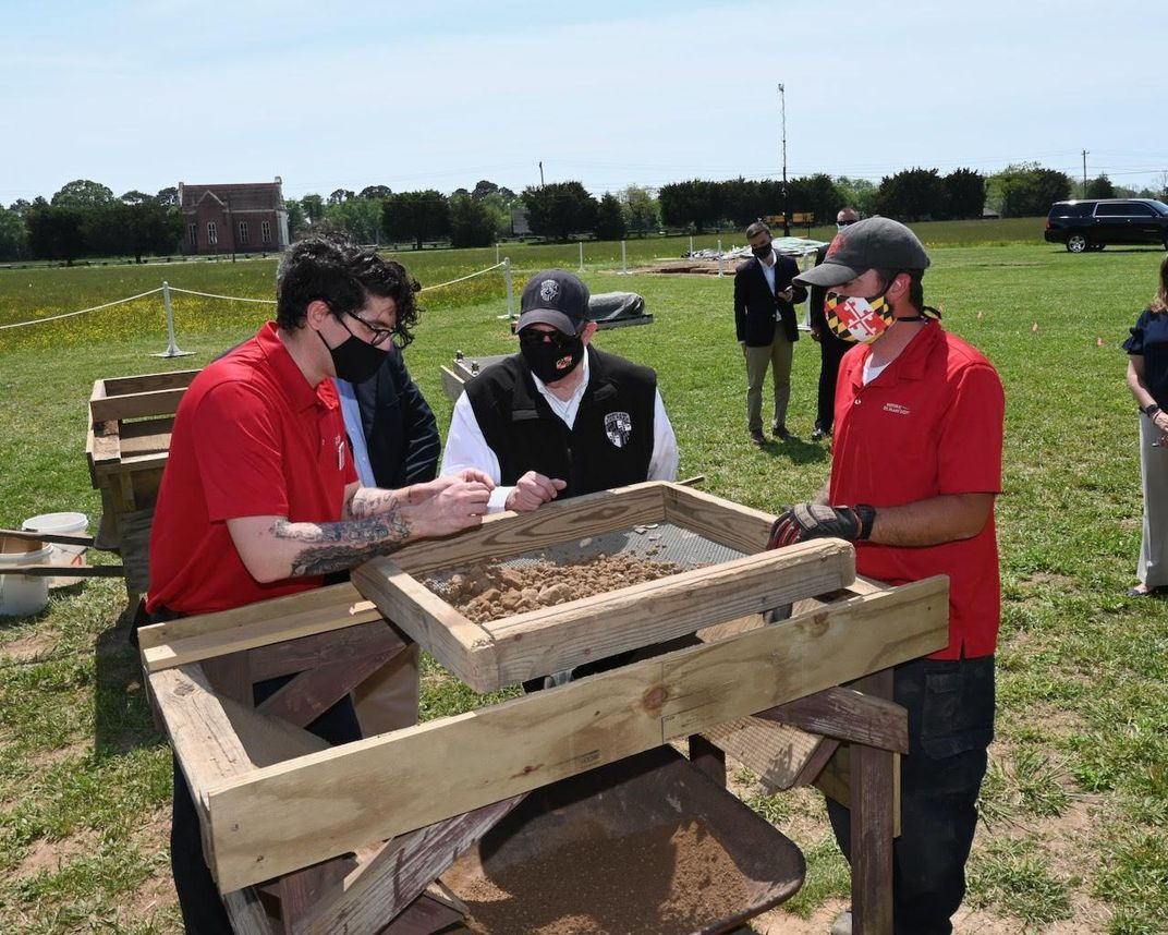 A group of people, some in red polo shirts and all wearing masks, stand outside in a field around a trough of dirt, examining an artifact