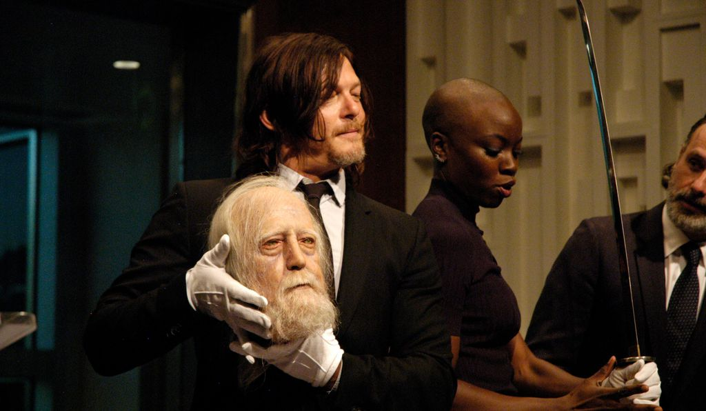 Actors Norman Reedus and a Danai Gurira show off Hershel's severed head and Michonne's samurai sword, respectively.