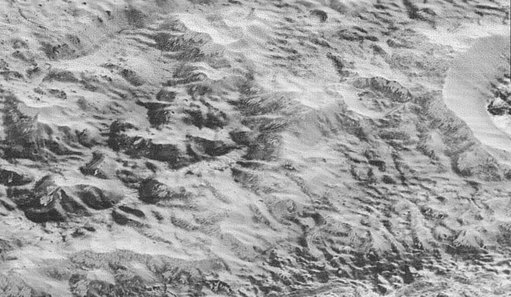 This image centers on the 'badlands' region of Pluto's icy crust. The mountains in the center are likely made of water ice, but shaped into dull peaks by the movement of nitrogen and other exotic ice glaciers over time.