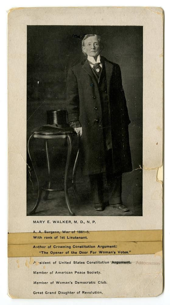 Dr. Mary Walker stands, leaning on a cane, next to a top hat. She wears a suit and glasses.