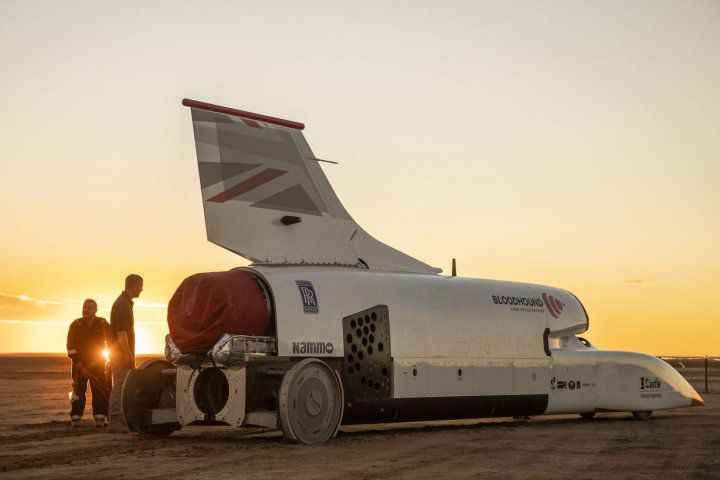 An image of the supersonic car at sunset with two people standing to its left.