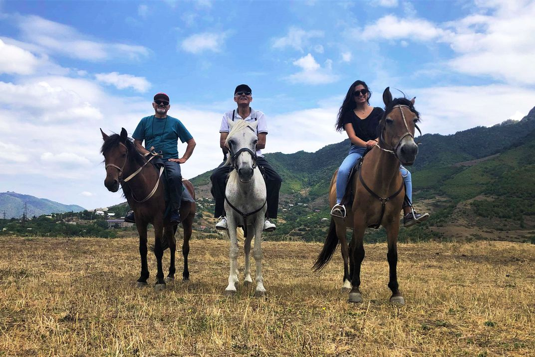 Three smiling people sit on horseback neck to each other.