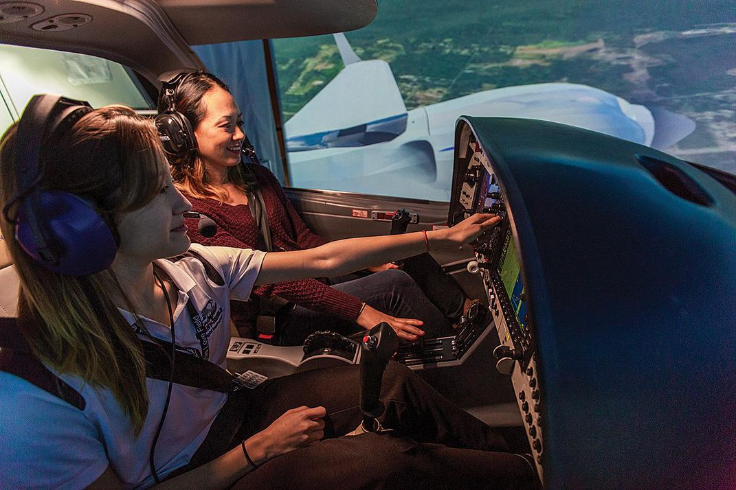 students practice flying on a simulator