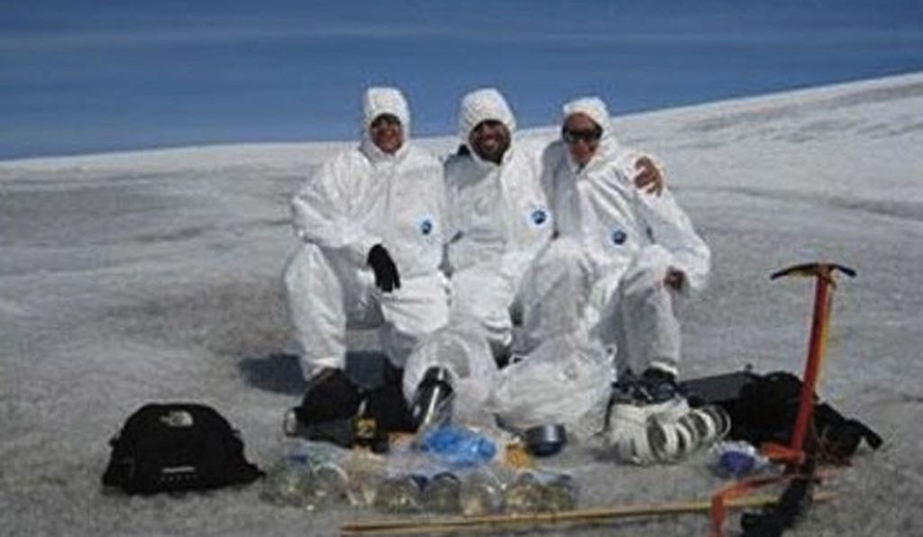 Researchers studying cryoconite holes must sometimes wear clean suits to prevent contaminating their microbial samples.