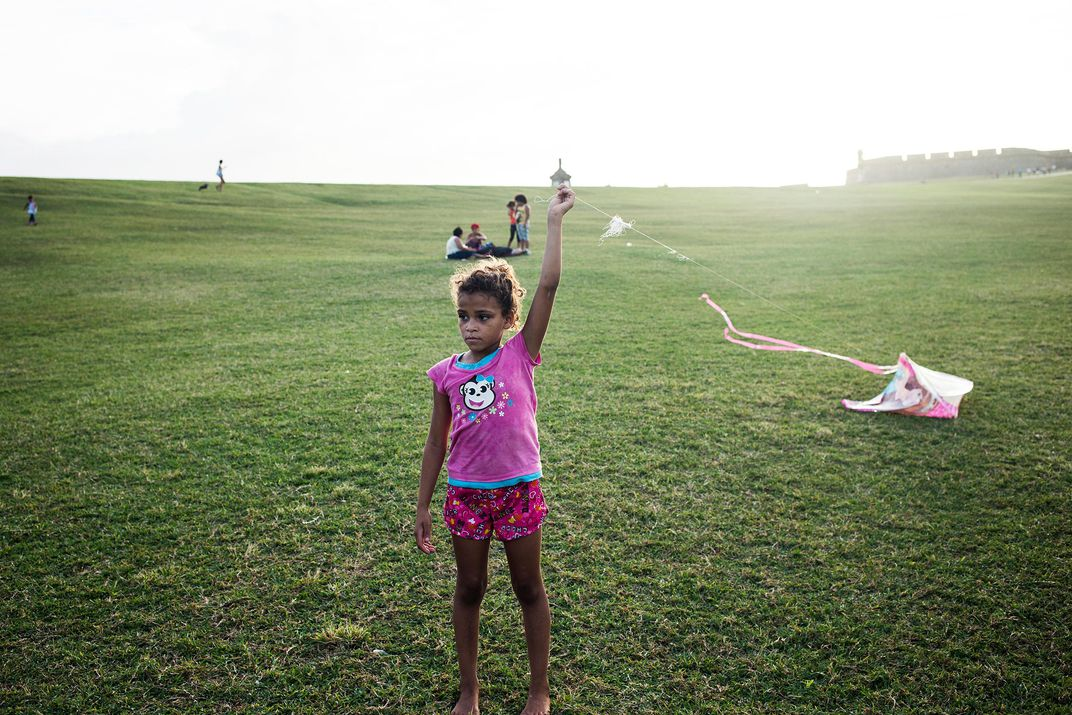 A little girl named Brenda flies a kite at El Morro fort by San Juan Harbor.