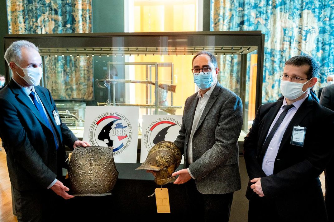 Three men stand around a table; two hold a piece of armor. The breastplate, left, is large and carved with a figure of a woman on its front; the helmet, right, is likewise intricate and has a curved brim that juts out