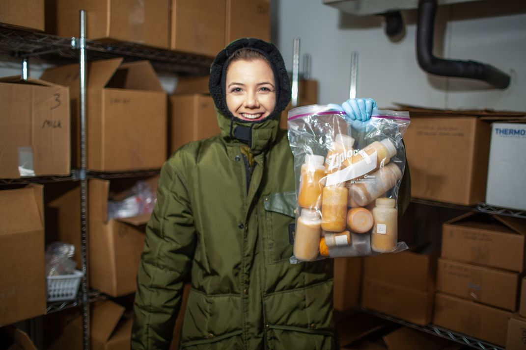 Nutrition lab research assistant Jenna Pastel stands inside the freezer that contains the animal milk repository. She's wearing full-body, hooded snowsuit and holding a bag of bottles of orange-colored animal milks.