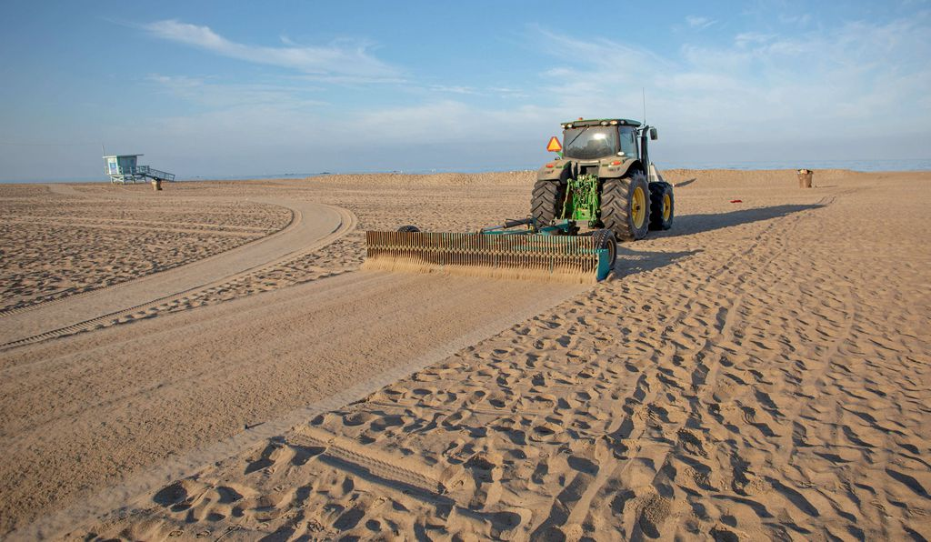 A rake attached to the back of a tractor leaves smooth sand in its wake, which is ideal for beachgoers but not for beach hoppers that get caught up in the tines.