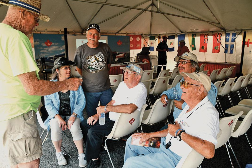 crowd of middle-aged to elderly people sitting and standing and talking at Oshkosh