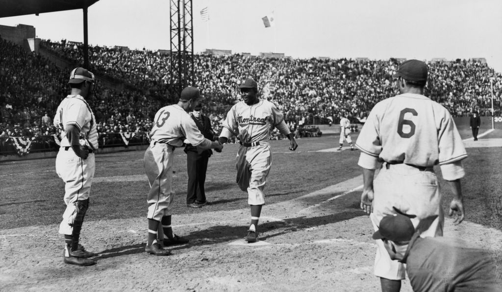 Jackie Robinson crosses homeplate after hitting a three-run home run, on Opening Day of the 1946 Montreal Royals season.