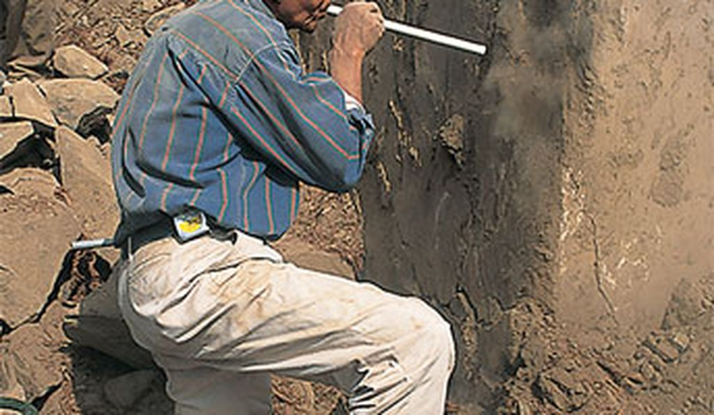 Researchers say the temple is a key to Andean civilization (Bernardino Ojeda blows dust from a mural).