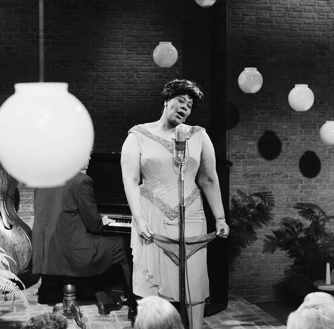 Fitzgerald stands, holding part of her dress in either hand, and tilts her head to her side as she sings with eyes closed and mouth open; she's surrounded by globe lamps and a piano player sits behind her