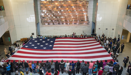Museum visitors participate in a flag folding while singing (or humming) the anthem (NMAH)