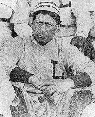 A black and white, slightly grainy image of a Native American man, facing the camera and sitting near other players in uniform, hands clasped in front of him and looking serious