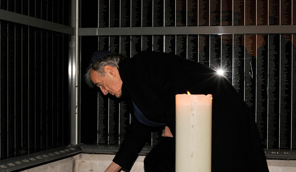 Elie Wiesel lights a candle for Holocaust victims on a memorial wall, which identifies tens of thousands of Hungarian Holocaust victims, in the Holocaust Memorial Center in Budapest, Hungary on Dec. 10, 2009.