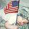 Baby A, wearing her daddy's hat and holding up an American Flag.