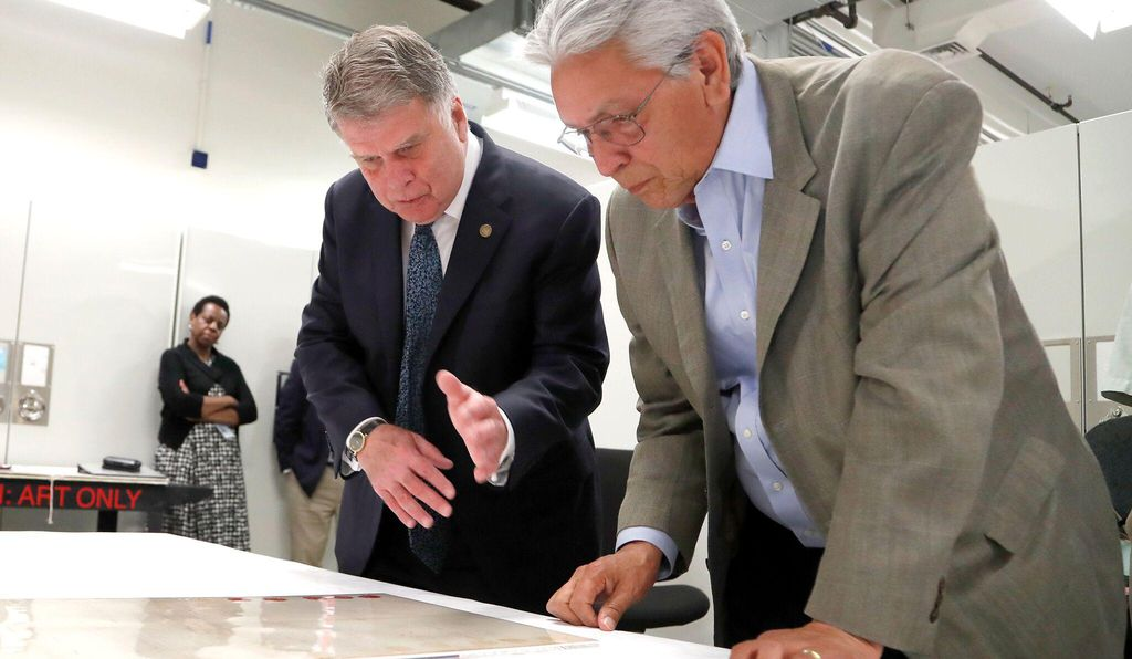Archivist of the United States David Ferriero and American Indian Museum director Kevin Gover examine the latest addition to