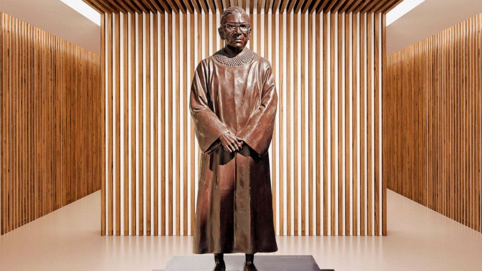 A bronze statue of a short white woman, wearing her Justice robes and standing simply with hands folded in front of her, wearing glasses and her hair in a bun