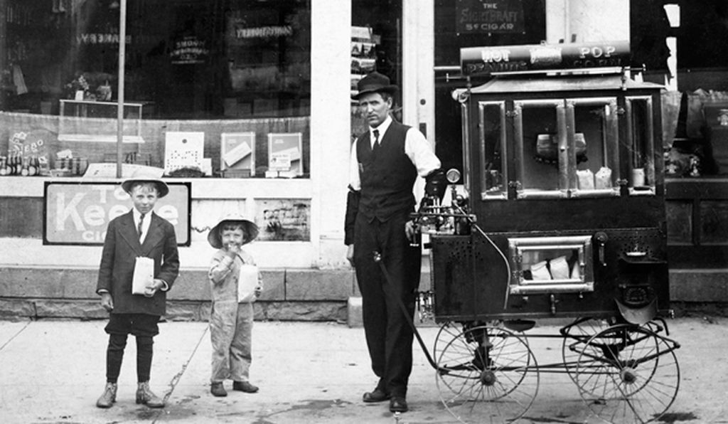 A street vendor sells popcorn to children in 1912 Illinois.