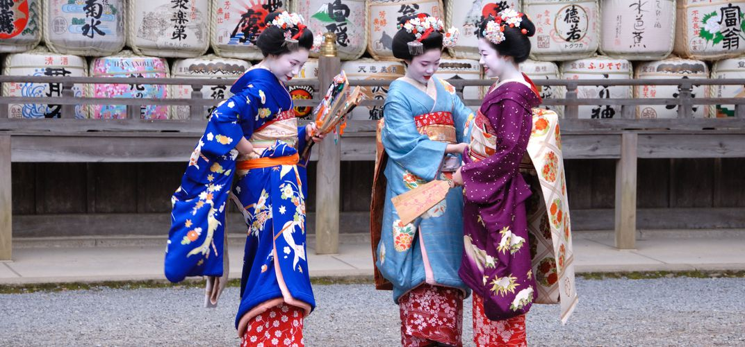 Young Geishas offer a picturesque pose against sake barrels