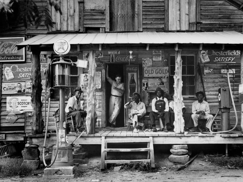 A group of people sit on the porch of a general store, surrounded by signs for products like Coca Cola and Chesterfield's cigarretes; most look at the camera