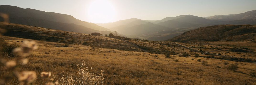 In the background, a setting sun casts a golden light over the mountains. In the middle of the landscape, a small farm and a few electrical polls can be seen in the distance.