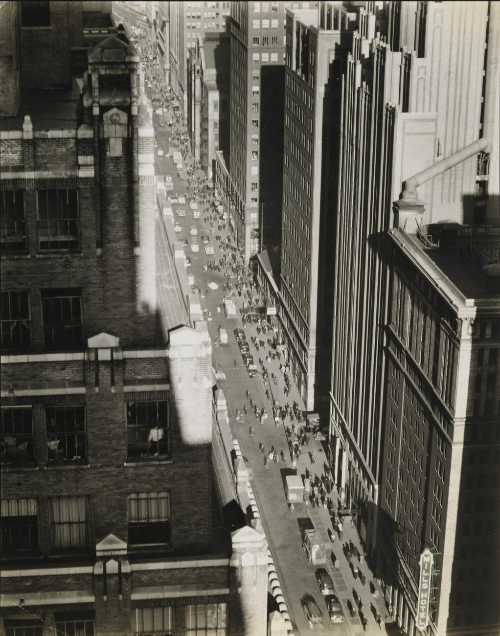 A black and white photograph looking down on a street in Manhattan