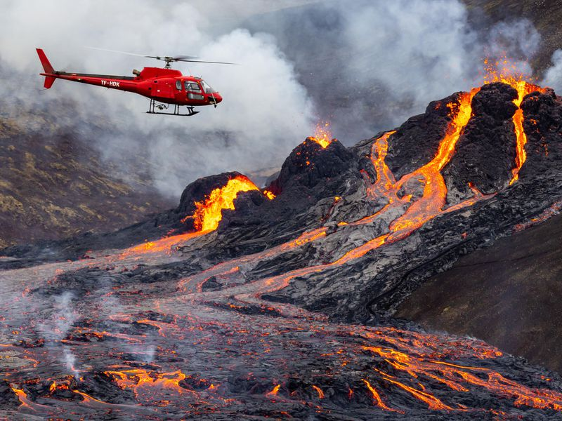 The photo shows a volcanic eruption. Magma is flowing down the volcano. A red helicopter hovers near the volcano.