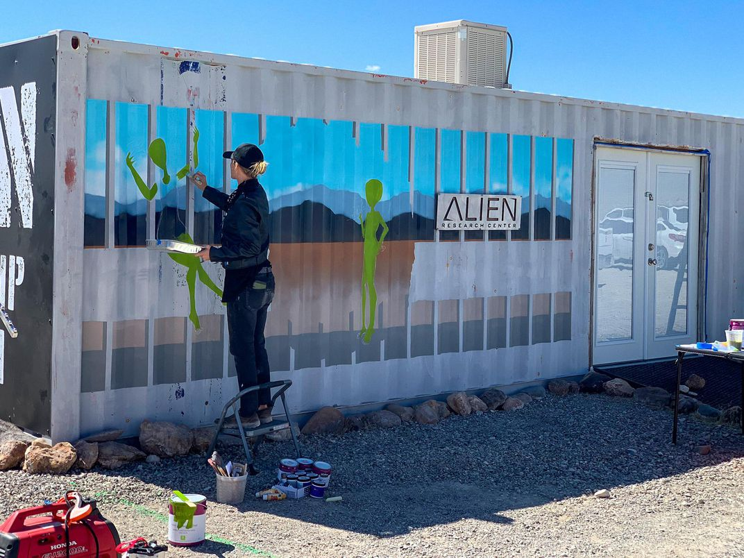 artist Brandy Whisenant paints a mural at the Alien Research Center