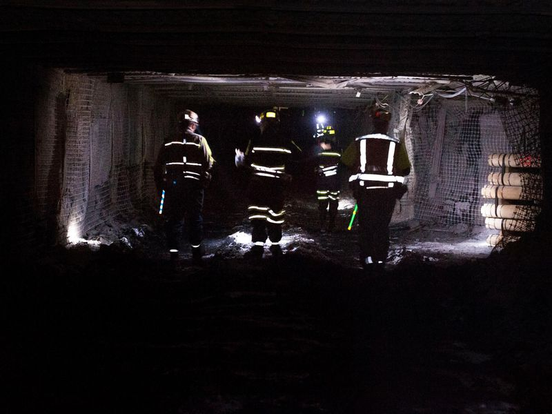 Coal miners dramatically walk through a tunnel