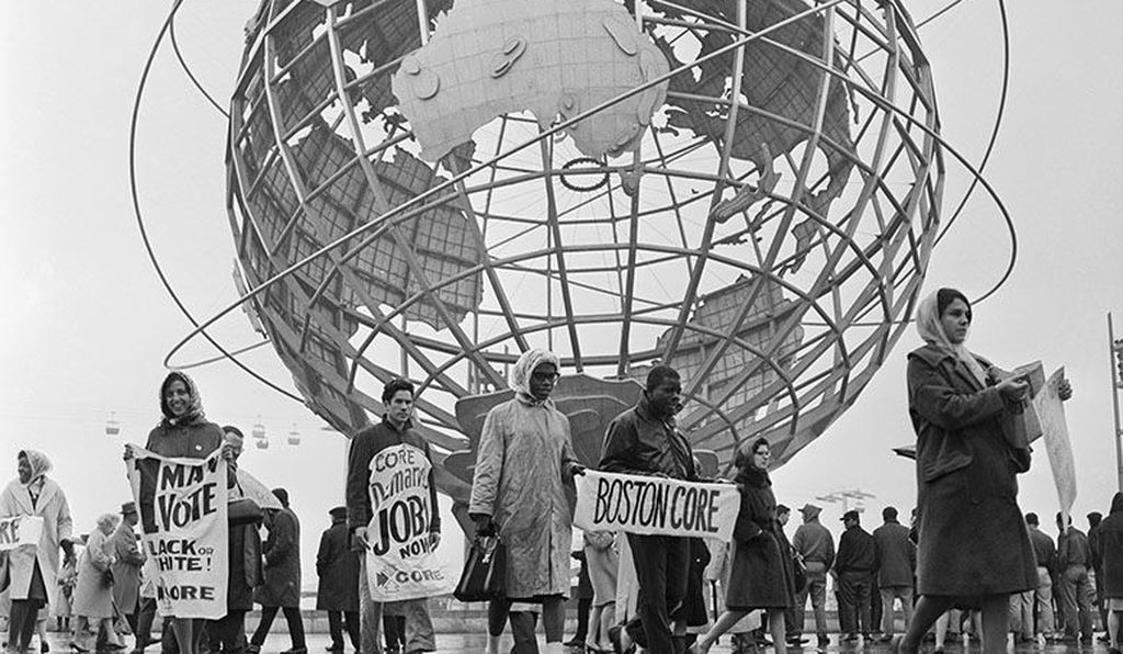On April 22, 1964, demonstrators from the Boston, Massachusetts chapter of CORE, march in the shadow of the Unisphere, the symbol of the World's Fair.