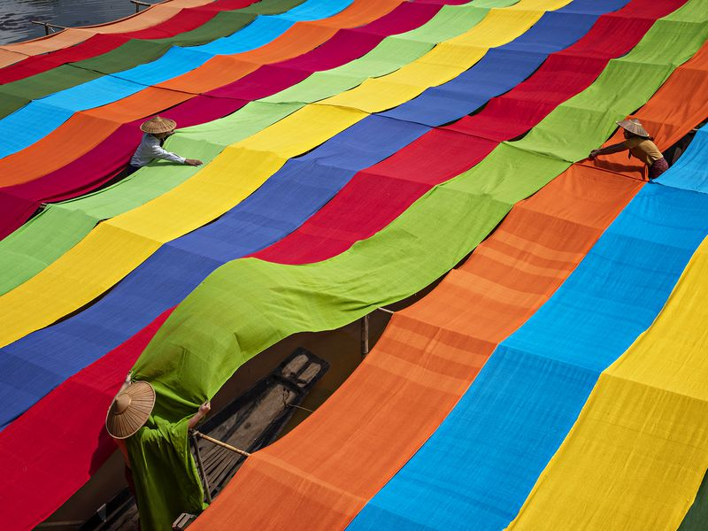 Locals at the inle lake drying the clothes in the sun after dye them with colors.