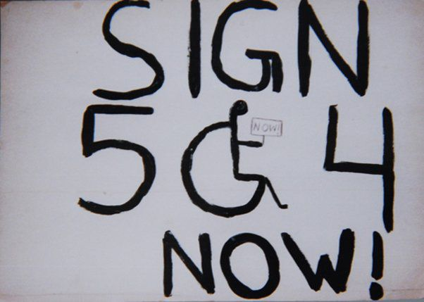 "A handwritten sign with black letters on white background, which reads ""Sign 504 Now!"" The ""O"" is a person sitting in a wheelchair, holding a smaller sign that says ""Now!"""