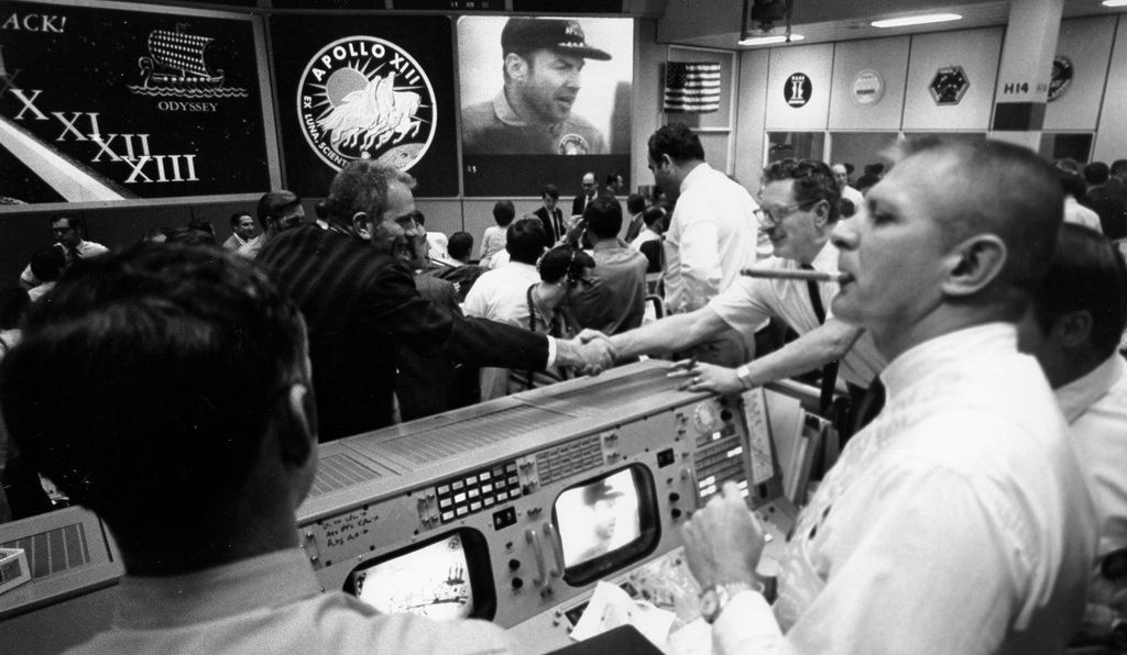 Flight Director Gene Kranz smokes a celebratory cigar, while others shake hands following the return of the crew on April 17, 1970.