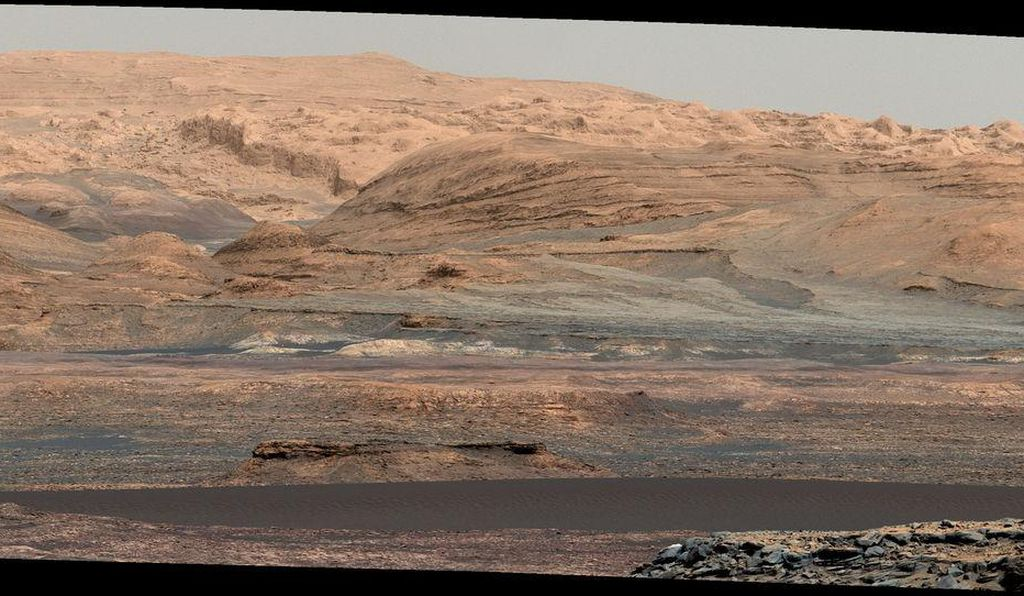The dark material at the bottom of this Curiosity panorama is part of the Bagnold dune field. The highest dunes are two stories tall. In the distance is Mt. Sharp.