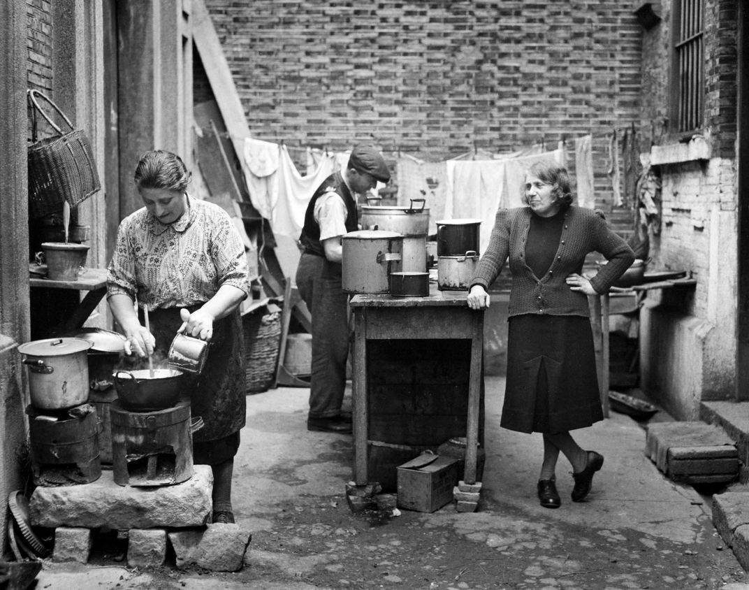 A black and white image of three people working in an outdoor kitchen, cooking with laundry hanging behind them