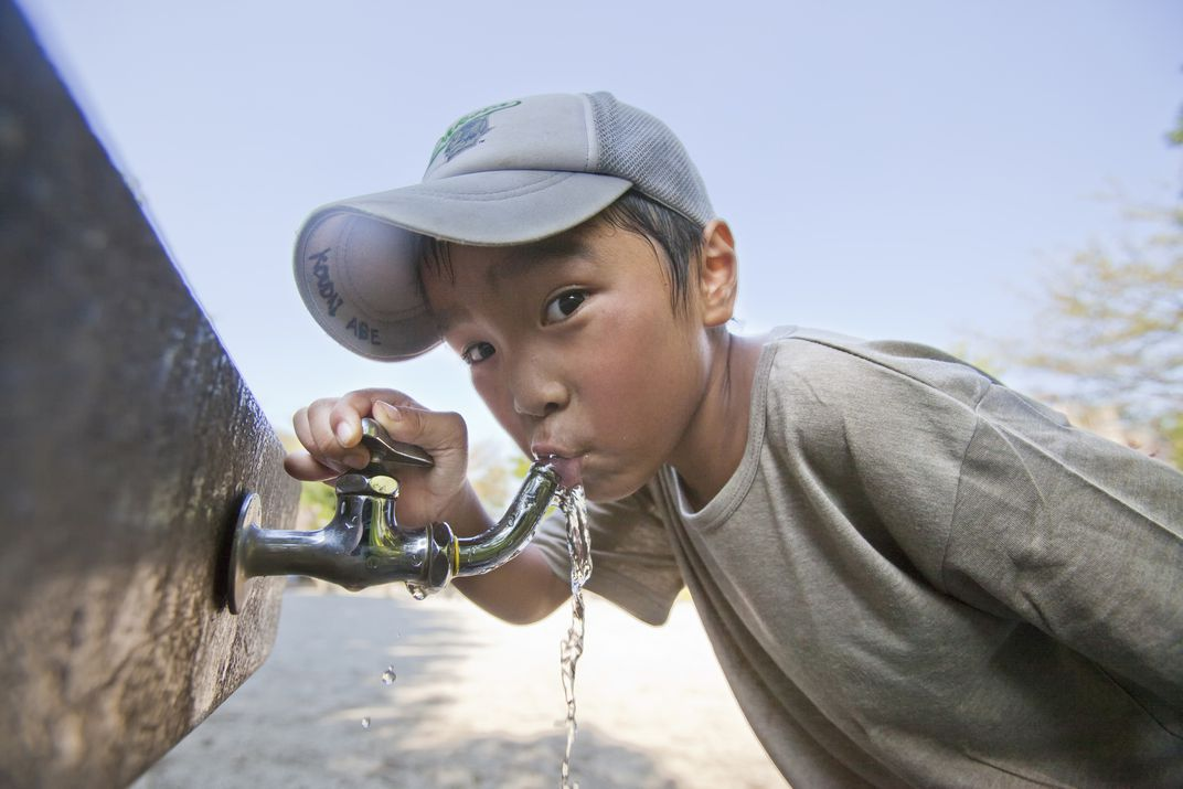 Image of child drinking from water faucet