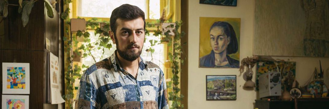 A young man faces the camera with a neutral look. On the walls behind him are a painted portrait of a women, some ivy growing on a light-filled window, and smaller paintings and objects.