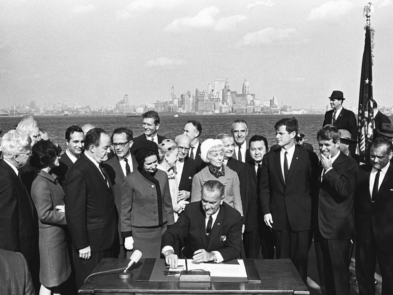 President Lyndon B. Johnson signs the Immigration Bill of 1965 on Liberty Island in New York Harbor.