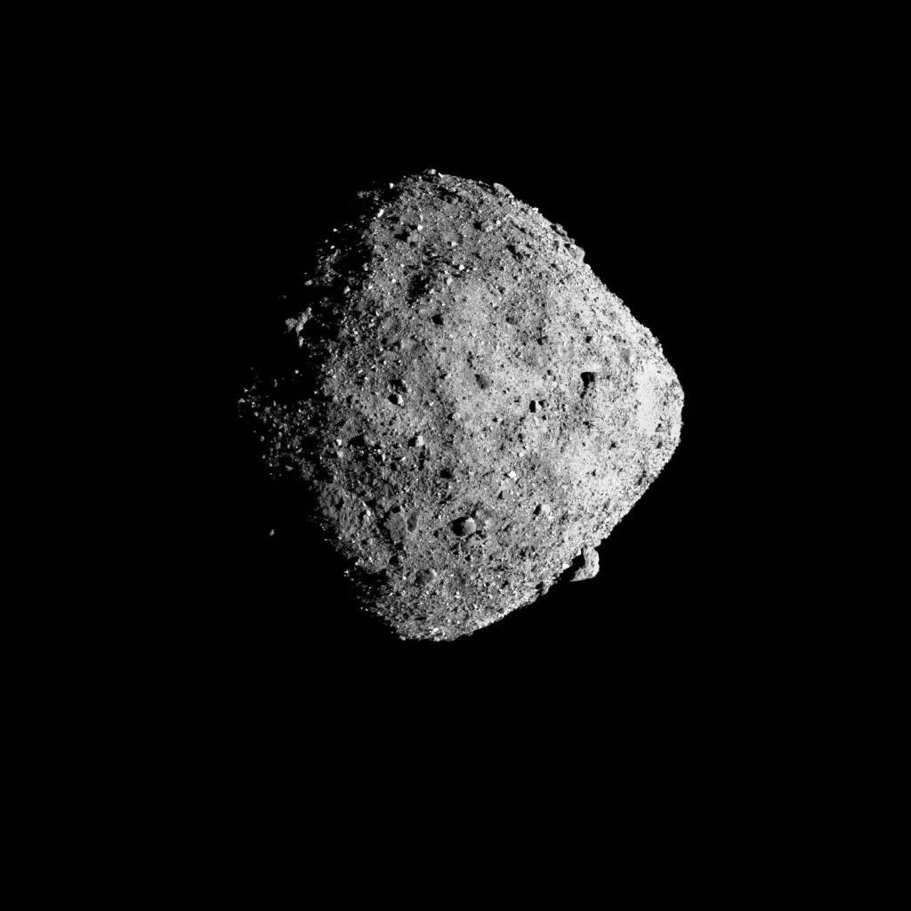A gray, round asteroid in the black depths of space.