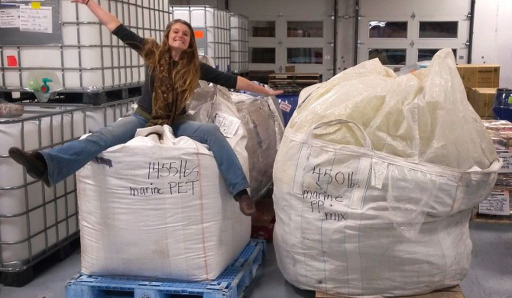 Chloé Dubois perches on a sack full of plastic marine debris gathered from the western shores of Vancouver Island last summer.