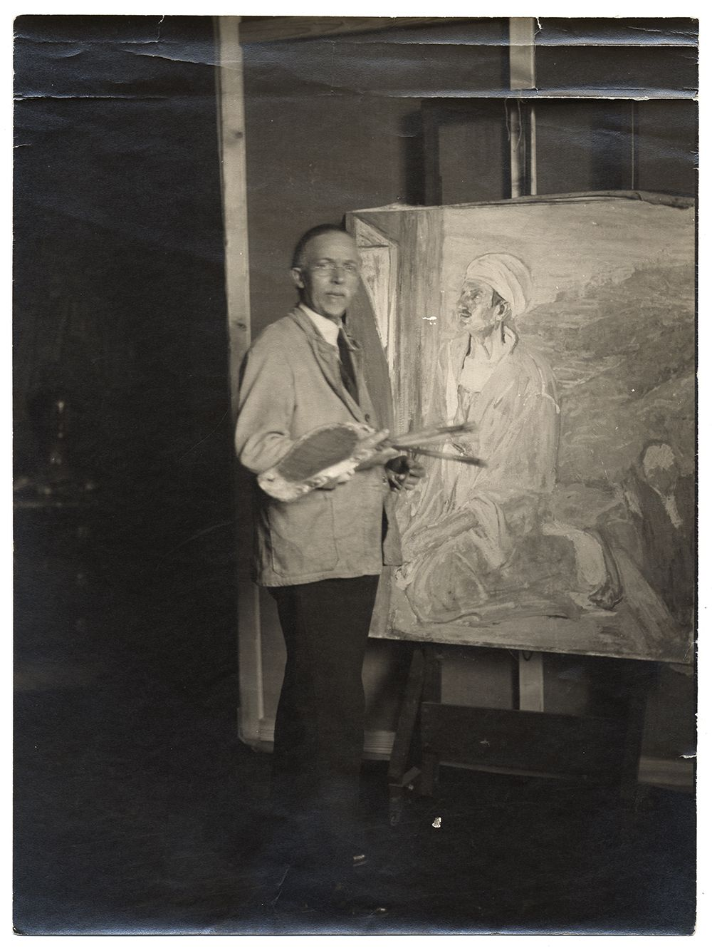 Henry Tanner in his studio next to his painting Judas.
