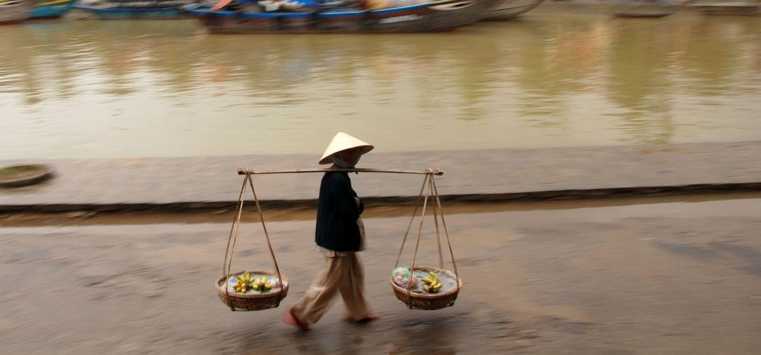 A fruit seller walks along the Thu Bon River in Hoi An