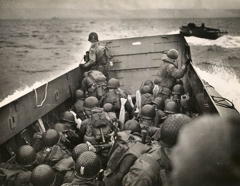 Tightly packed troops crouch inside their LCVP as it plows through a wave.jpg