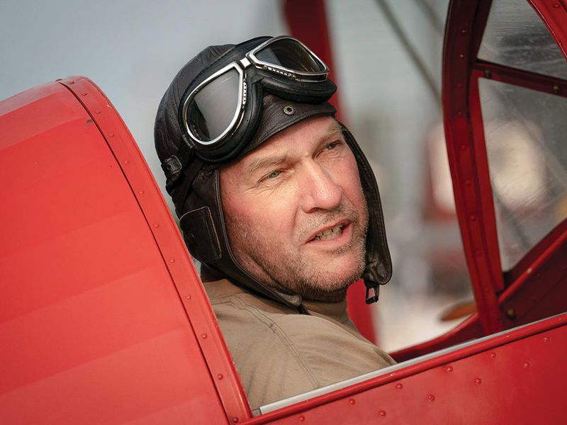 Andrew King wearing a vintage helmet and goggles in red cockpit