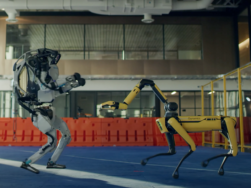 The humanoid Atlas robot dances on the left side of the image, and the canine-like Spot robot dances on the right