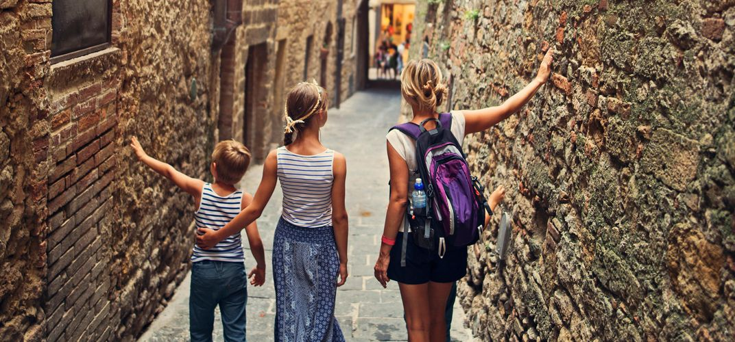 Mother at children exploring a Tuscan town