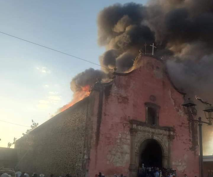 Huge clouds of dark smoke billow from the top of the old, sixteenth-century church