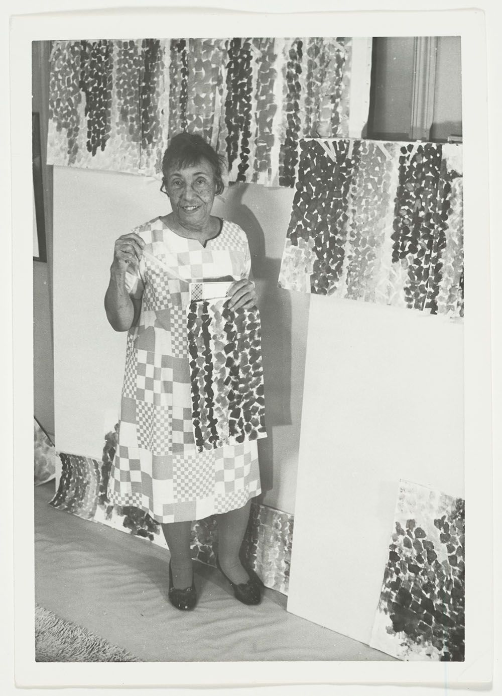 Photograph of Alma Thomas showing off Alma's Stripes in her studio