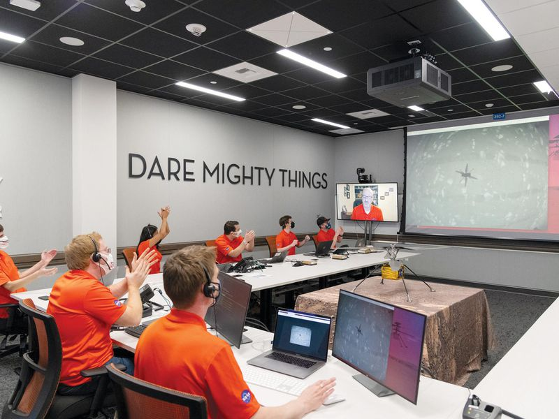 team of people in orange shirts sitting and clapping while looking at a screen